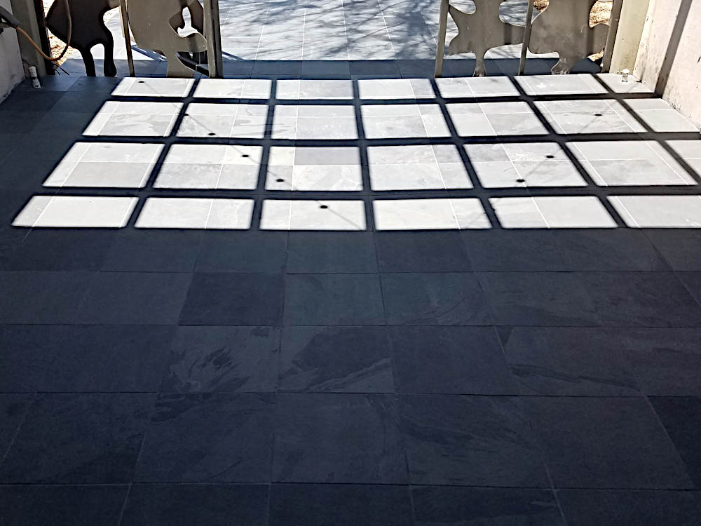This is a closeup picture of 12 x 12 gauged black slate after being grouted with Dove Gray grout