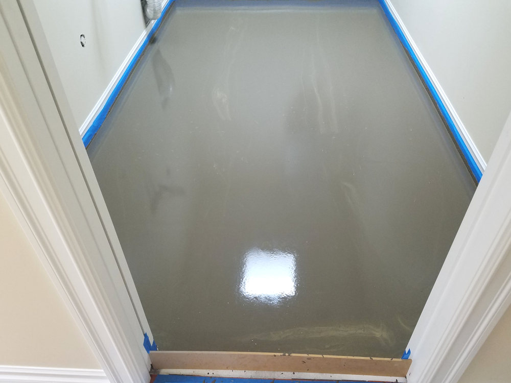 This is a picture of a fresh pour of Ardex self leveling underlayment in a laundry room
