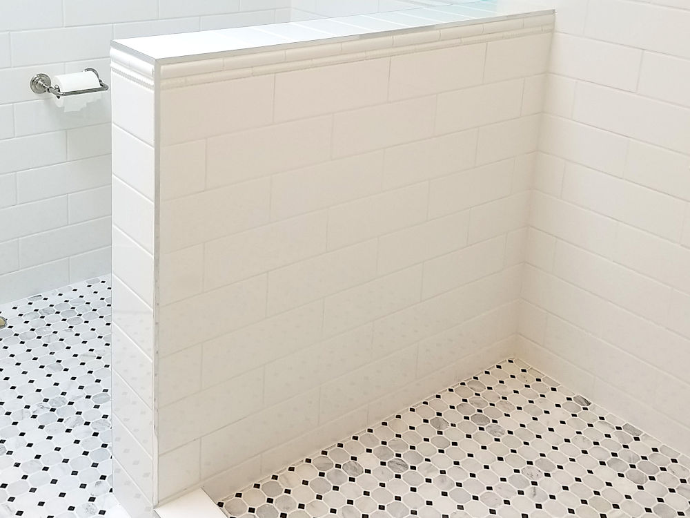 This is a picture of a pony wall in a shower with white subway tile and Schluter Jolly installed on it