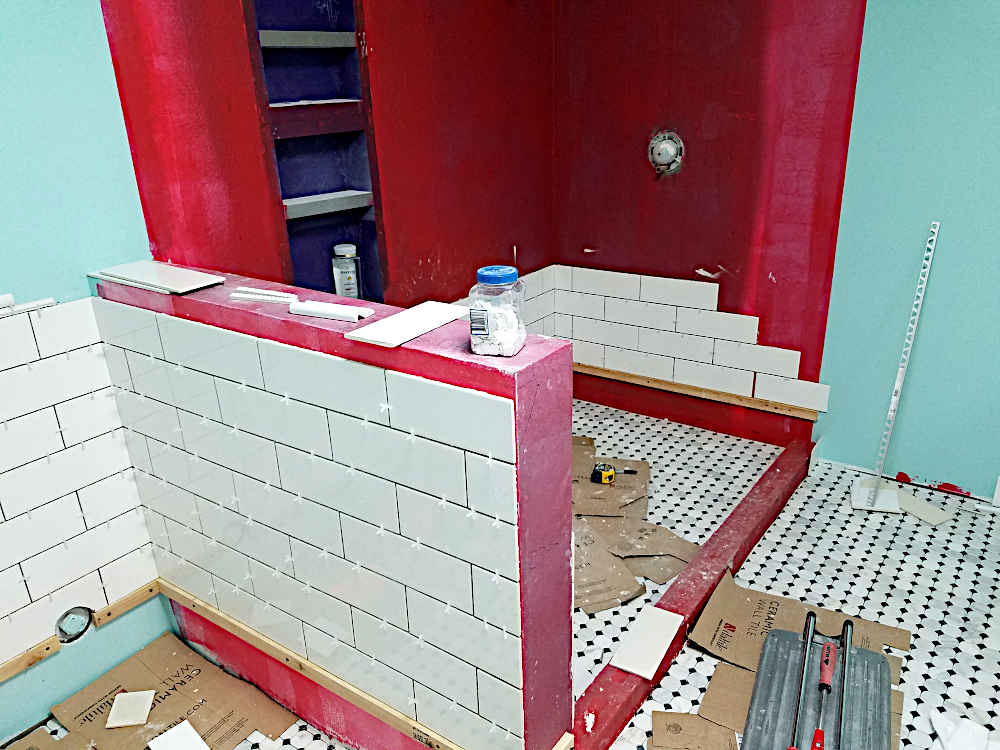 This is a picture of tile being installed around the outside of a pony wall