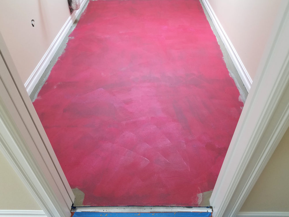 This is a picture of a laundry room floor with RedGard applied to the surface