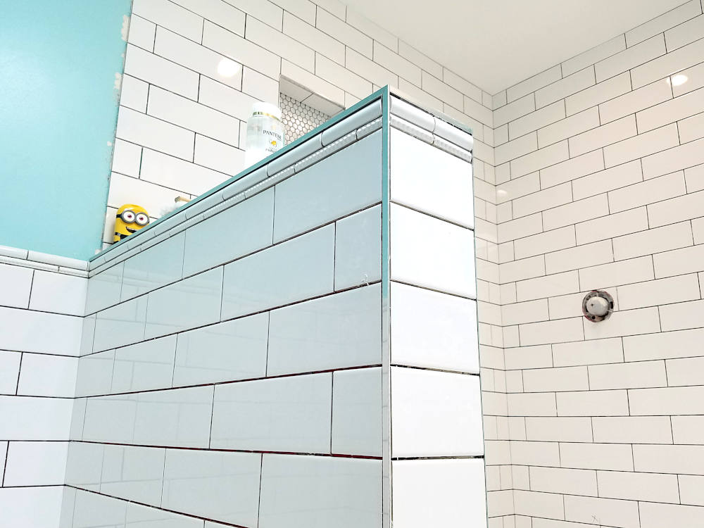 This is a picture of white subway tile with deco liners installed on a pony wall in a bathroom shower