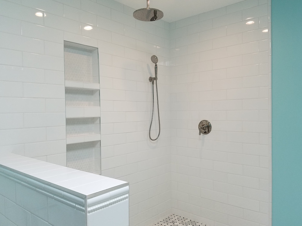 This is a picture of a shower with white subway tile and chrome Schluter Jolly