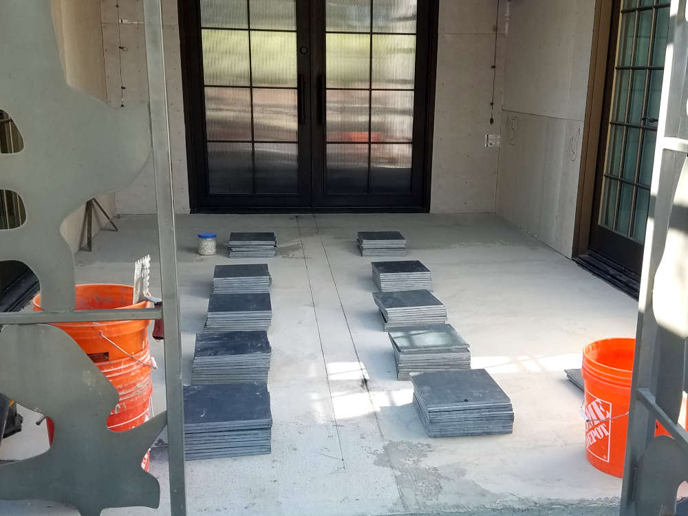 This is a picture of 12 x 12 black slate installation in progress with the slate in small stacks and the chalk lines snapped
