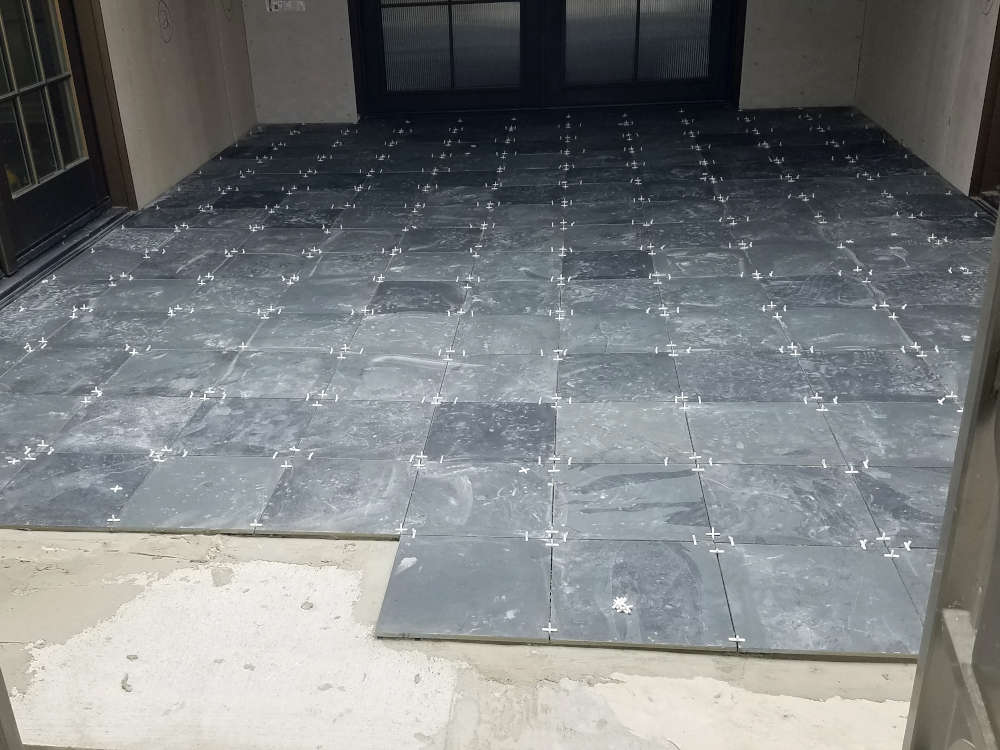 This is a picture of 12 x 12 gauged black slate being installed on a patio