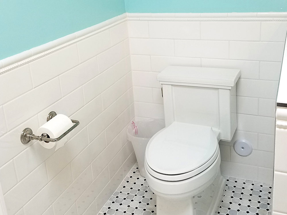 This is a picture of a white subway tile installed around a toilet
