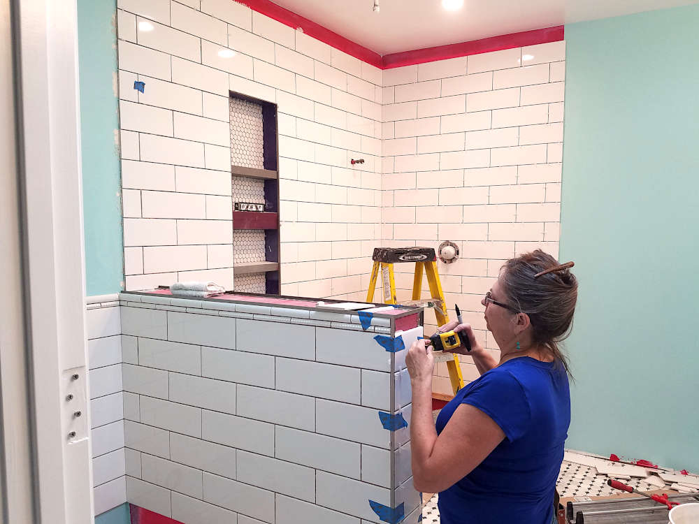 This is a picture of one of the owners of KDB Flooring installing tile on a pony wall in a shower
