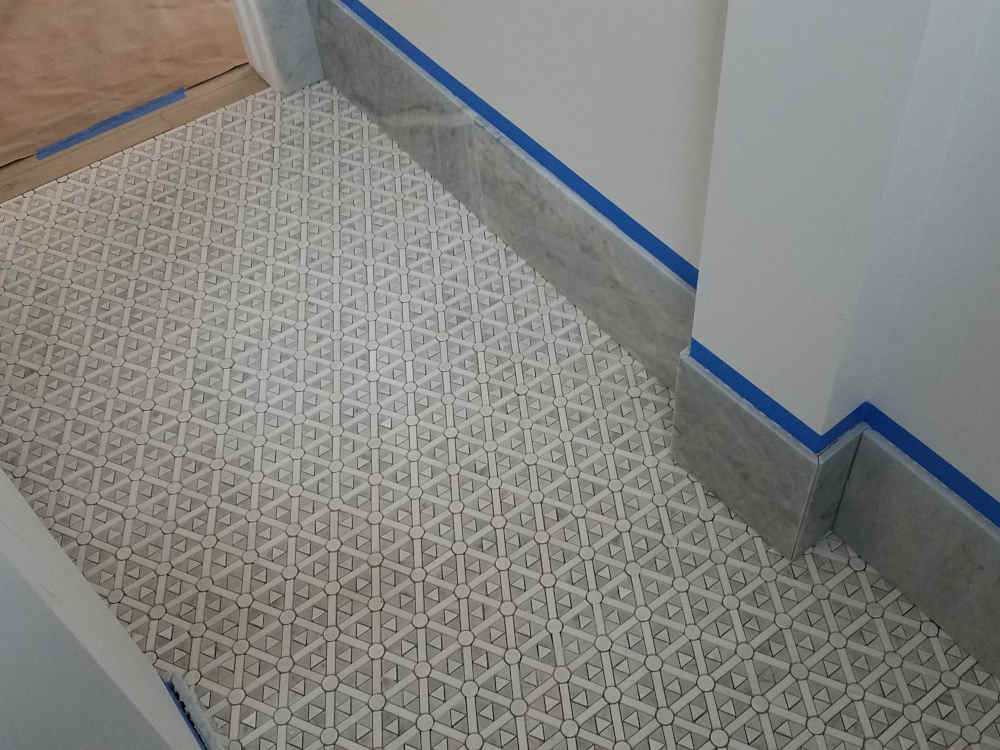 This is a picture of Mesh-mount Marble with 9 1/4 inch marble base cut with mitered corners installed on a Powder Room floor