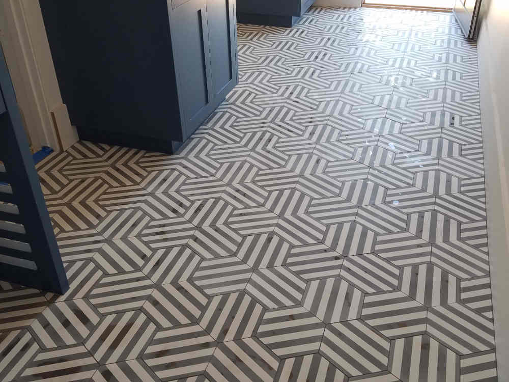 This is a picture of Concrete tiles with black and white stripes installed in a pattern on a Laundry room floor