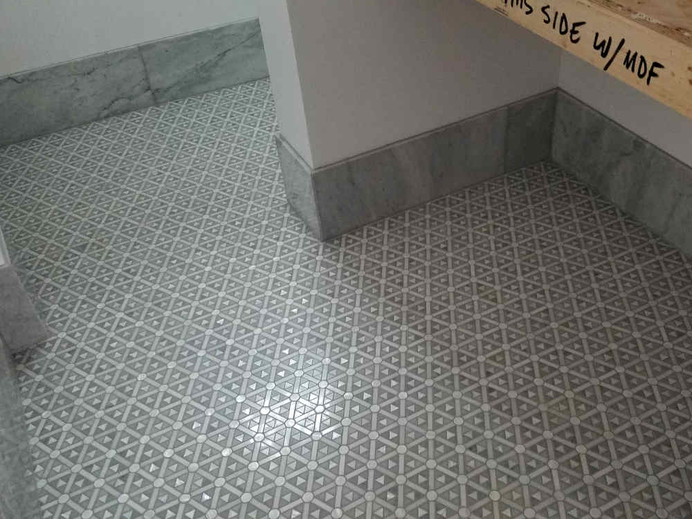 This is a picture of a Marble mesh-mount tile with a Mother of Pearl overlay and 9.25 inch Marble base installed on a Powder room floor
