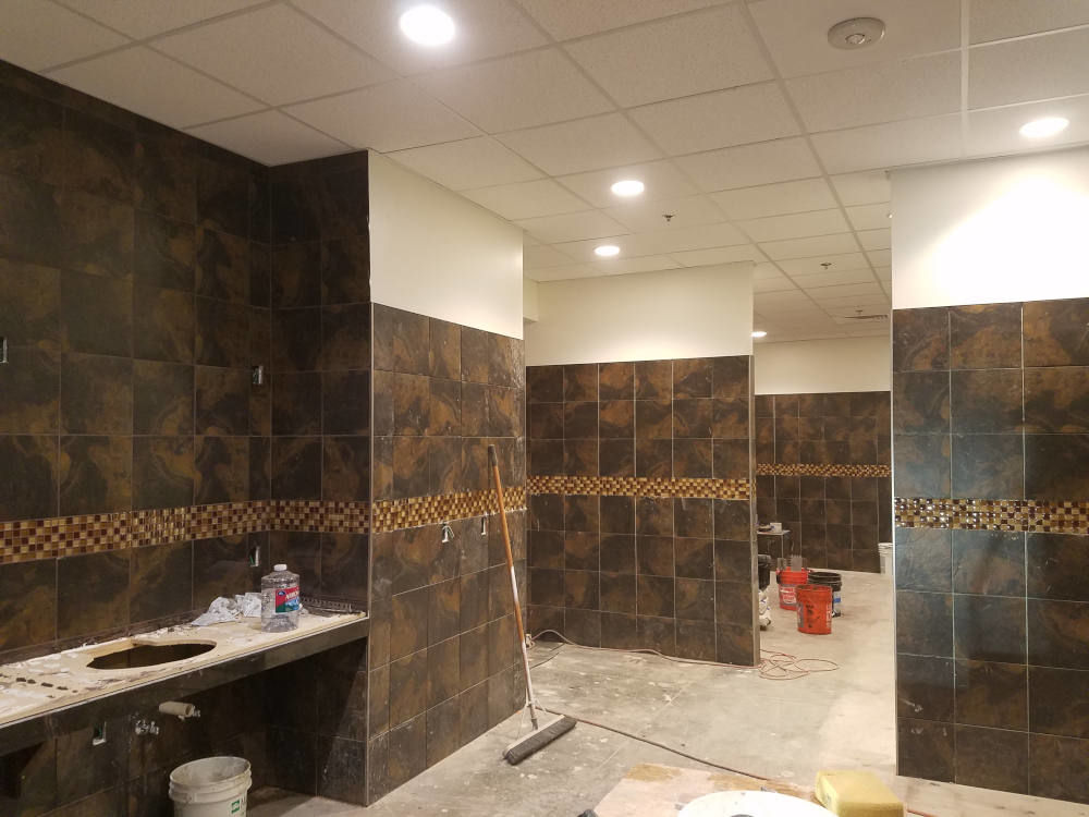 This is a picture of a 4 inch Daltile glass band installed on the walls of a men's locker room