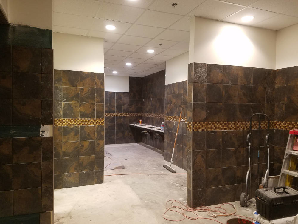 This is a picture of 12 x 12 ceramic tile being installed on walls in a gym locker room