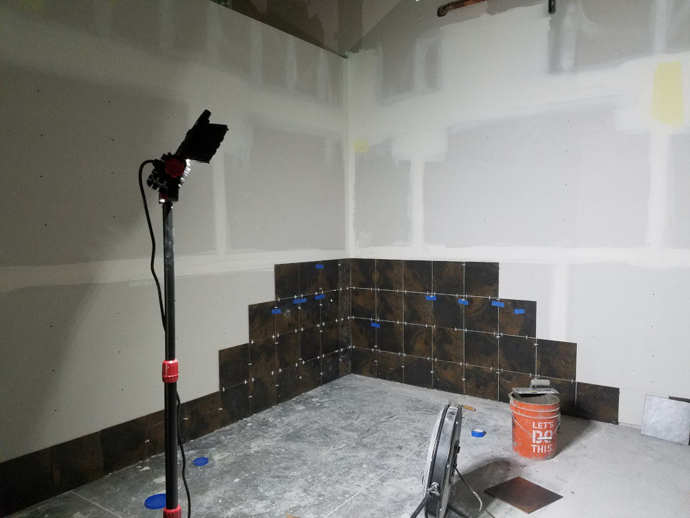 This is a picture of 12 x 12 ceramic tile being installed on the walls of a men's locker room