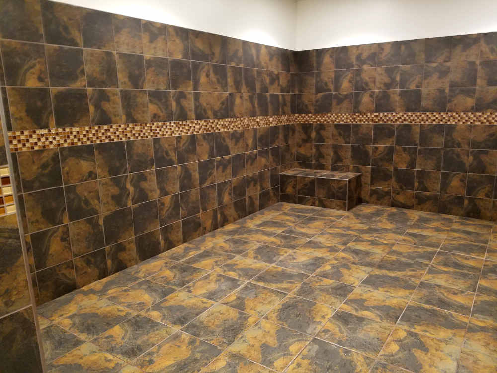 This is a picture of ceramic tile floors and walls with a 4 inch glass band