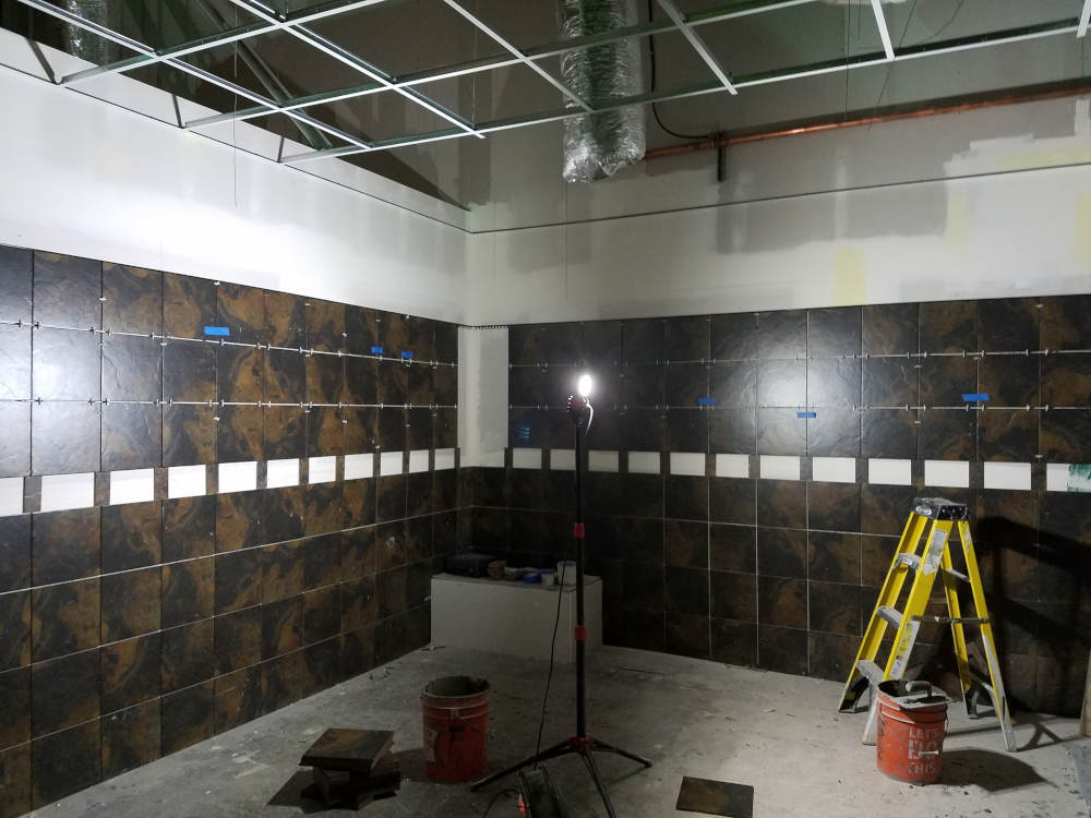 This is a picture of ceramic tile being installed on bathroom walls at a gym with a space left out for a 4 inch glass band