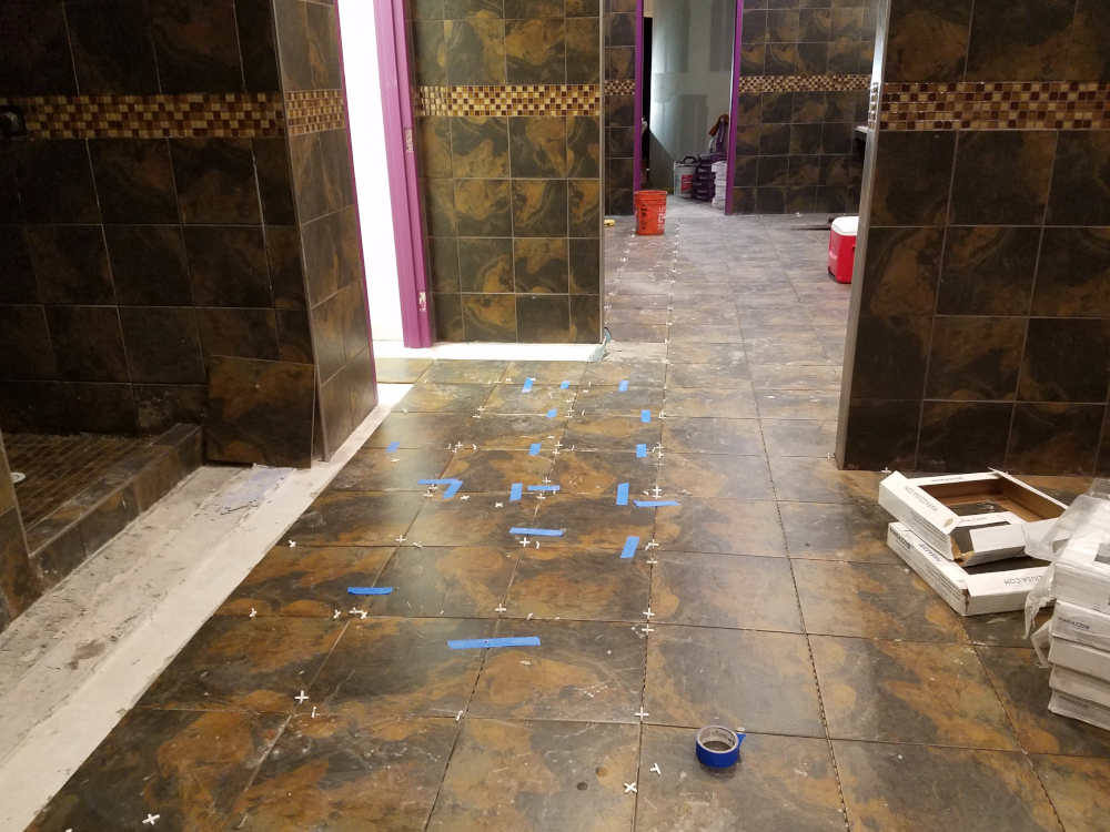 This is a picture of ceramic tile that is being installed to slope to a drain on a gym locker room floor