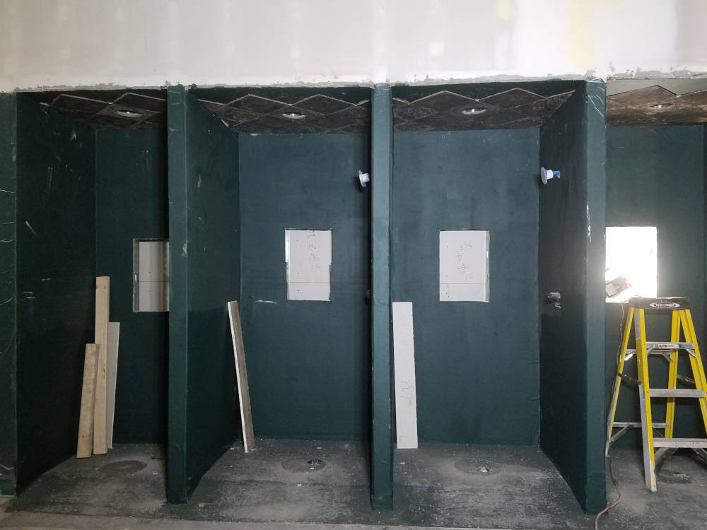 This is a picture of four showers after being waterproofed using Mapei Aquadefense