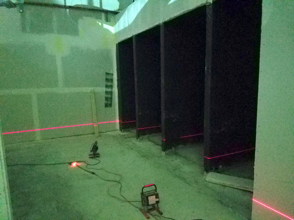 This is a picture of four gym showers being laid out using a laser for leveling