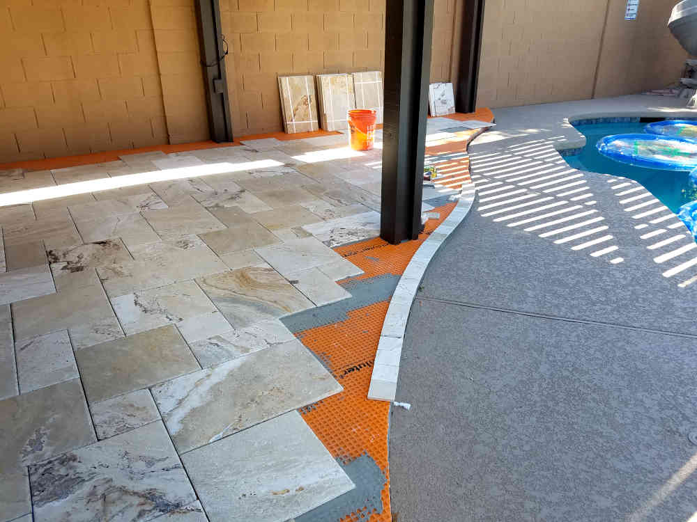 This is a picture of 4 x 4 Bullnose Travertine tile being installed on a curved step on a patio by a pool in Phoenix