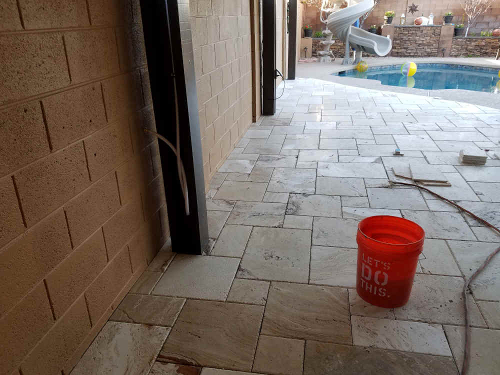 This is a picture of Travertine stone being cut against a block wall on a back patio